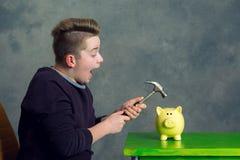 Piggybank abierto del adolescente con el martillo Fotos de archivo libres de regalías