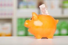 Piggybank amarelo com nota do Euro no contador da farmácia fotografia de stock