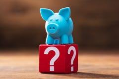 Piggybank auf rotem Block mit Fragezeichen stockfoto