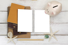 Piggybank on blank white notebook with passports and a pencil on. Top view of pink piggybank on blank white notebook with passports and a pencil on wooden Royalty Free Stock Photos