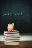 Piggybank and books in front of chalkboard Stock Image