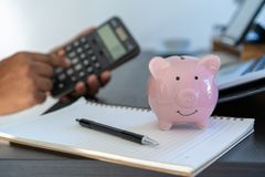 piggybank And Calculator On Desk business document calculator co stock photography