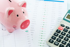 Piggybank and calculator, stock market. Piggybank and calculator on white backgrond, stock market Stock Photo