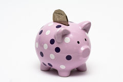 Piggybank with a coin in it. Polka dotted piggy coin with one coin sticking out of it Royalty Free Stock Photography
