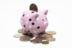 Piggybank with a coin in it and around it. Piggy bank with pile of coins spread around it and one inserted into it Stock Photos