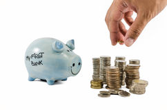 Piggybank and coins with hand on white background Stock Images