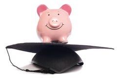 Piggybank con el sombrero de la tarjeta del mortero Foto de archivo libre de regalías
