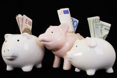 Piggybank con el vario dinero en circulación Imagenes de archivo