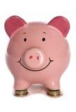 Piggybank, das auf Poundmünzen stillsteht Stockbild