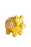 Piggybank de Goldy en las flores aisladas imagenes de archivo
