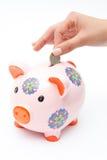 Piggybank del euro de la mano de la mujer Fotos de archivo libres de regalías