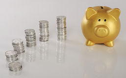 Piggybank dourado com moedas Fotos de Stock