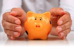 Piggybank e mãos. Imagens de Stock