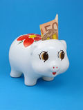 Piggybank with euro note. White piggybank with a 50 euros note, on blue background Royalty Free Stock Images