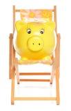 Piggybank giallo su deckchair Immagine Stock