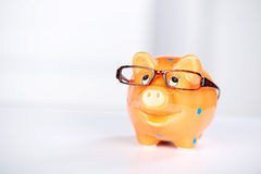 Piggybank With Glasses On Desk Royalty Free Stock Images