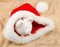 Piggybank guarding Santa's crisis budget Royalty Free Stock Images
