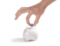 Piggybank and hand. Isolated on white background Royalty Free Stock Photography