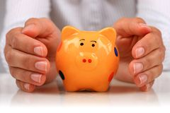 Piggybank and hands. Stock Images