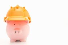 Piggybank with hard hat. On white background stock photography