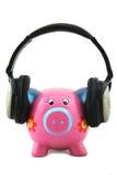 Piggybank with headphone. Isolated Piggybank with headphone shot over white background Royalty Free Stock Photo