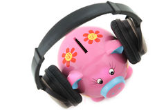 Piggybank with headphone. Isolated Piggy bank with headphone shot over white background Royalty Free Stock Image