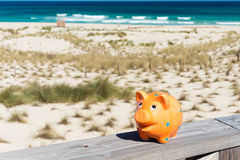 Piggybank in holidays. Piggybank standing on stage by the beach Stock Images