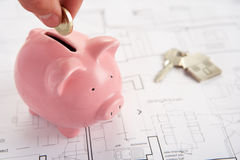 Piggybank with house plans and keys. And hand putting coin in piggybank royalty free stock photos