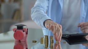 Piggybank med det doktorand- locket, besparingar för utbildning, man som räknar kostnader stock video