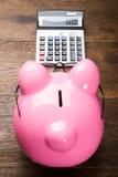 Piggybank mit Taschenrechner auf Tabelle Stockfotografie