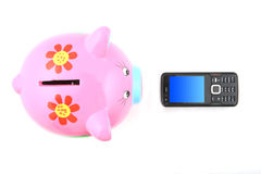 Piggybank and Mobile Phone. Isolated piggyback and mobile phone shot over white background. Focus is on the piggyback Stock Photography