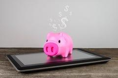 Piggybank na tabuleta imagem de stock royalty free