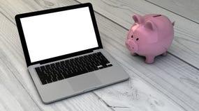 Piggybank och bärbar dator Royaltyfri Foto