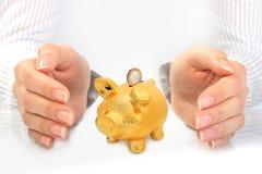 Piggybank och händer. Royaltyfri Fotografi