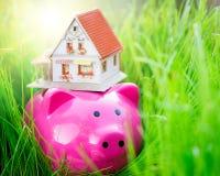 Piggybank och hus Arkivbild