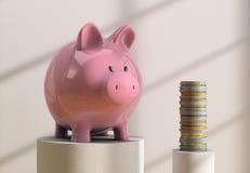 Piggybank och mynt Arkivbilder