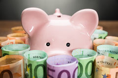 Piggybank omgav med eurosedlar Arkivbilder