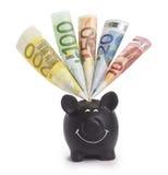 Piggybank preto muito feliz enchido com as várias euro- cédulas Foto de Stock