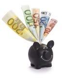 Piggybank preto muito feliz enchido com as várias euro- cédulas Imagem de Stock