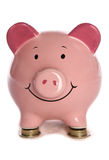 Piggybank que se reclina sobre monedas de libra Imagen de archivo