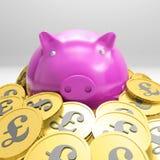 Piggybank rodeó en las monedas que mostraban Gran Bretaña Fotos de archivo libres de regalías