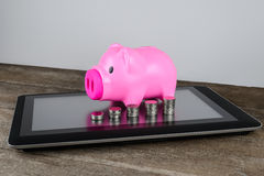 Piggybank and row of coin money on tablet. In money saving, online Banking, internet Banking concept Stock Photography