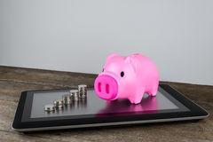 Piggybank and row of coin money on tablet. In money saving, online Banking, internet Banking concept Royalty Free Stock Image