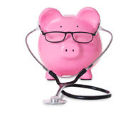 Piggybank With Stethoscope And Eyeglasses. Isolated over white background royalty free stock photos