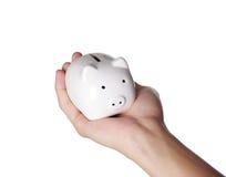 Piggybank und Hand Lizenzfreie Stockfotos