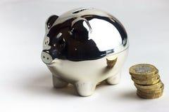 Piggybank und Stapel von Münzen lizenzfreie stockbilder