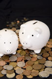 Piggybank with various currency. Piggy bank with various international currencies on a black background Stock Photos