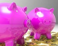 Piggybanks auf Pfund-Münzen-Show-Großbritannien-Finanzen Lizenzfreie Stockfotos