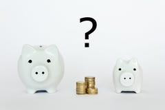 2 piggybanks coins question mark Stock Photos