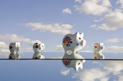 Piggybanks on mirror and sky Stock Photography